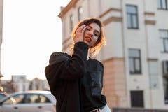 Giovane donna alla moda moderna graziosa con trucco naturale con le labbra sexy in una maglietta alla moda in un cappotto d'avang fotografia stock libera da diritti