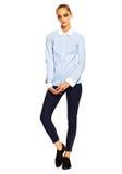Giovane donna alla moda in panno casuale dietro fondo bianco Fotografie Stock
