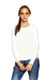 Giovane donna alla moda in panno casuale dietro fondo bianco Immagine Stock