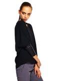 Giovane donna alla moda in panno casuale dietro fondo bianco Fotografia Stock