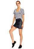 Giovane donna alla moda in panno casuale dietro fondo bianco Immagini Stock Libere da Diritti