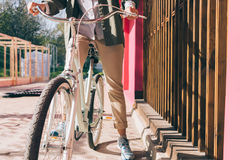 Giovane donna alla moda su una bicicletta blu in una città fotografie stock libere da diritti