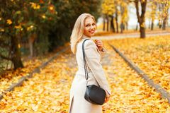 Giovane donna alla moda alla moda in un cappotto classico con una borsa fotografia stock