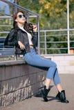 Giovane donna alla moda in vestiti di stile della roccia, bomber nero, blue jeans, calzamaglia in una griglia sotto i jeans avari Fotografie Stock Libere da Diritti