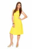 Giovane donna alla moda in vestito giallo che posa sul backgro bianco Immagine Stock