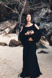 Giovane donna alla moda in vestito nero elegante all'aperto Fotografia Stock Libera da Diritti