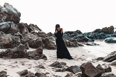 Giovane donna alla moda in vestito nero elegante sulla spiaggia di pietra Immagini Stock Libere da Diritti