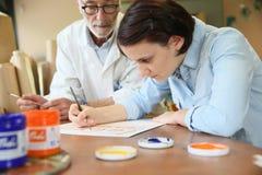 Giovane donna alla scuola con professore che studia pittura Immagini Stock