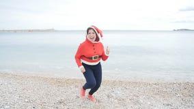 Giovane donna allegra in cappello di Santa che balla all'aperto video d archivio