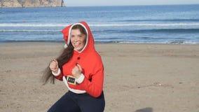 Giovane donna allegra in cappello di Santa che balla all'aperto archivi video