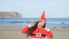 Giovane donna allegra in cappello di Santa che balla all'aperto stock footage