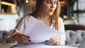 Giovane donna allegra che ascolta la musica con le cuffie e che per mezzo del computer portatile video d archivio