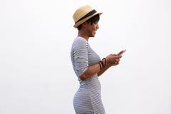 Giovane donna allegra che cammina e che manda un sms Immagini Stock