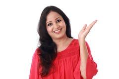 Giovane donna allegra che gesturing una mano aperta fotografia stock libera da diritti