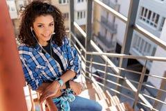 Giovane donna allegra che gode della vista della città dalla scala Fotografia Stock