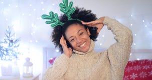 Giovane donna allegra che indossa i corni verdi della renna Fotografia Stock