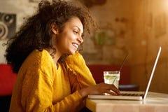 Giovane donna allegra che lavora al computer portatile in caffè Fotografia Stock Libera da Diritti