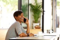 Giovane donna allegra che parla sul telefono cellulare Immagine Stock
