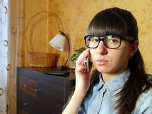Giovane donna allegra che parla sul telefono cellulare a casa Immagini Stock