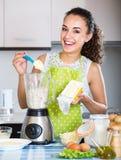 Giovane donna allegra che per mezzo del miscelatore della cucina immagini stock
