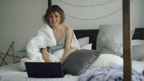 Giovane donna allegra che per mezzo del suo computer portatile che si siede a letto a casa video d archivio