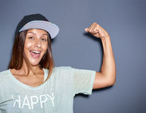 Giovane donna allegra che pompa i suoi muscoli immagine stock