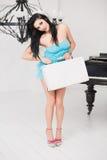 Giovane donna allegra che porta una valigia in una stanza leggera Fotografie Stock