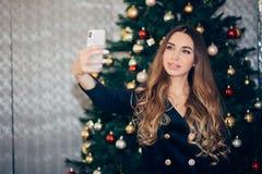Giovane donna allegra che prende un selfie di Natale con lo smartphone fotografie stock libere da diritti