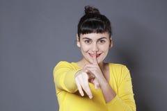 Giovane donna allegra che riconosce qualcuno che chiede la discrezione fotografia stock libera da diritti