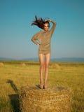 Giovane donna allegra che salta sulla pila del fieno Fotografie Stock Libere da Diritti