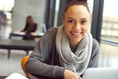 Giovane donna allegra che si siede nella biblioteca Fotografie Stock Libere da Diritti
