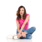 Giovane donna allegra che si siede su un pavimento Fotografia Stock Libera da Diritti