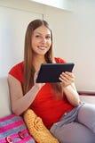 Donna che tiene il pc e sorridere della compressa Fotografia Stock