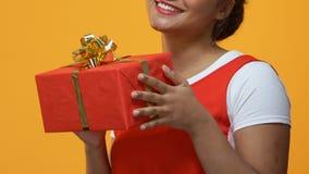Giovane donna allegra che tiene le mani attuali, regalo di occasione, sorpresa di anniversario video d archivio