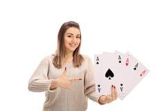 Giovane donna allegra che tiene quattro assi ed indicare Fotografie Stock