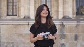 Giovane donna allegra con capelli scuri in maglietta nera che prende le foto r video d archivio