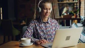 Giovane donna allegra in cuffie che ascolta la musica facendo uso del computer portatile in caffè video d archivio