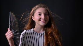Giovane donna allegra felice che smazza con il fan d'annata e che accoglie qualcuno, sorridendo, isolato su fondo nero video d archivio