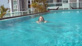 Giovane donna allegra felice nella serie rossa di nuoto nella piscina Bella acqua del turchese di giorno soleggiato stock footage