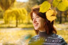 Giovane donna allegra nel parco di autunno che sorride un giorno soleggiato fotografia stock