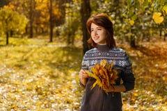 Giovane donna allegra nel parco di autunno che sorride un giorno soleggiato immagini stock