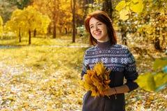 Giovane donna allegra nel parco di autunno che sorride un giorno soleggiato fotografie stock libere da diritti