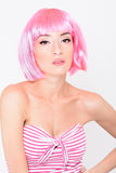 Giovane donna allegra in parrucca rosa che posa sul fondo bianco Fotografia Stock