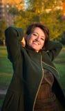Giovane donna allegra in un cappotto verde nel parco di autunno al tramonto fotografie stock libere da diritti