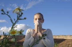 Giovane donna allergica che starnutisce in un prato Fotografia Stock