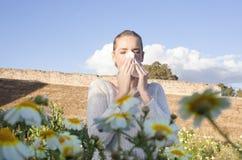 Giovane donna allergica che starnutisce in un prato Fotografie Stock Libere da Diritti