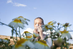 Giovane donna allergica che starnutisce in un prato Immagini Stock