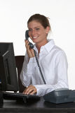 Giovane donna allo scrittorio che comunica sul telefono Fotografia Stock Libera da Diritti