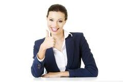 Giovane donna allo scrittorio che gesturing BENE Fotografie Stock