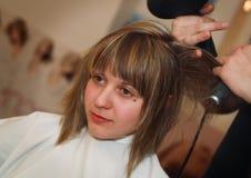 Giovane donna allo studio dei capelli Fotografia Stock